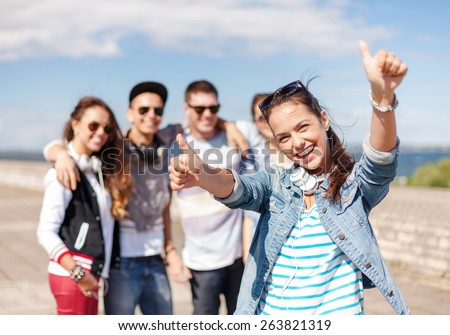 summer holidays and teenage concept - teenage girl in sunglasses and headphones hanging out with friends outside and showing thumbs up #263821319