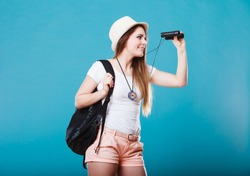 Summer holidays and tourism concept. Lovely tourist woman with backpack compass looking through binoculars on blue