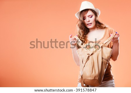 Summer holidays and vacation. Girl in fashionable clothes straw hat holding bag handbag looking for something. Woman on brown