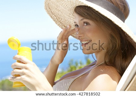 summer holidays and vacation - girl putting sun protection cream at the beach
