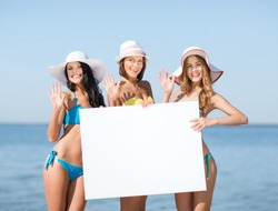 summer holidays and vacation - girls in bikinis holding blank white board on the beach