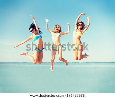 summer holidays and vacation - girls jumping on the beach #196783688