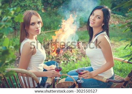 summer holidays and vacation - girls with red wine glasses near bonfire