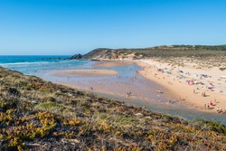 Summer holidays at Amoreira beach with riverside flowing into the Atlantic Ocean - sports and families in the idyllic seascape of the Vicentine Coast Natural Park, Aljezur - Algarve PORTUGAL