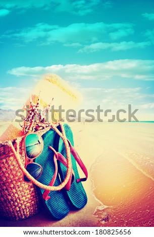 Summer holidays bag, sun glasses and flip flops on a tropical beach