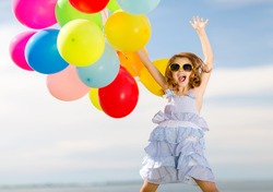 summer holidays, celebration, children and people concept - happy jumping girl with colorful balloons outdoors