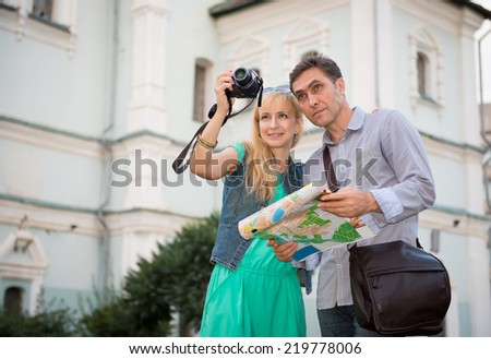 Summer holidays, dating and tourism concept  middle aged couple with camera and city map. Happy tourists sightseeing city with map.