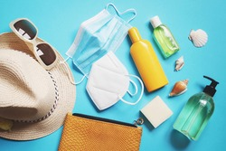 Summer holidays 2021 during coronavirus. Abroad travelling in the time covid. Lifting international travel restrictions. Beach essentials and disposable face mask, respirator and sanitizer