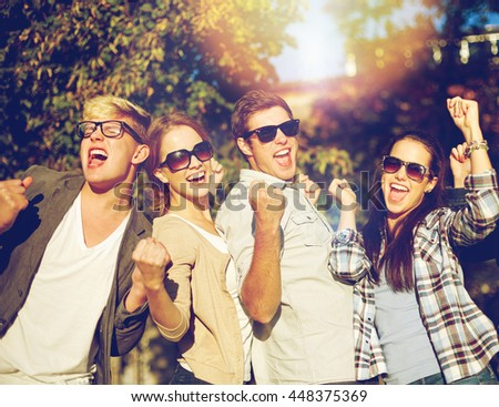 summer holidays, friendship, achievement and success concept - group of happy friends showing triumph gesture at campus or city park