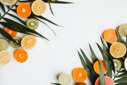 Summer holidays, resort vacation, exotic fruits background. Summertime vibes. Composition with citrus slices on white surface, copy space