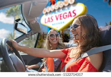 summer holidays, road trip and travel concept - happy young women driving in convertible car and laughing over welcome to fabulous las vegas sign background