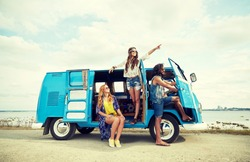summer holidays, road trip, vacation, travel and people concept - smiling young hippie friends in minivan car on beach