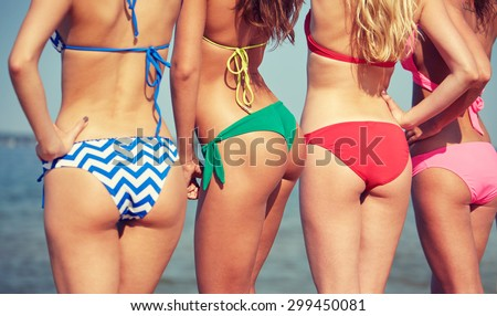 summer holidays, travel, body care and people concept - close up of happy young women on beach from back