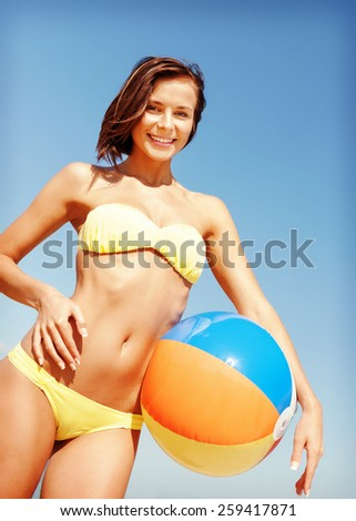 summer holidays, vacation and beach activities concept - girl in bikini with ball on the beach