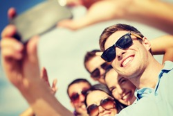 summer, holidays, vacation and happiness concept - group of friends taking selfie with smartphone