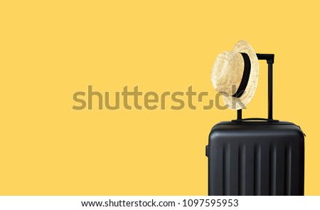 Summer holidays, vacation and travel concept. Suitcase or luggage bag with sun hat on yellow background for copy space.