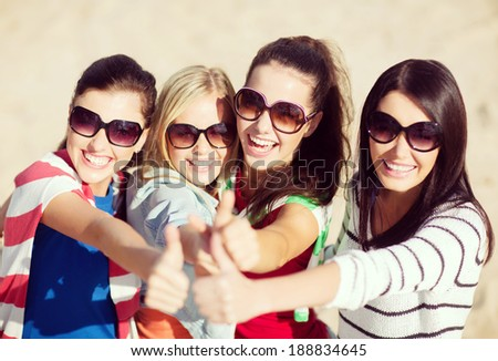 summer holidays vacation happy people concept beautiful teenage girls or young women showing thumbs up