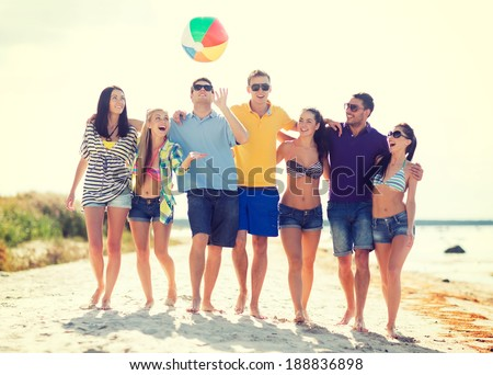 summer, holidays, vacation, happy people concept - group of friends having fun with ball on the beach
