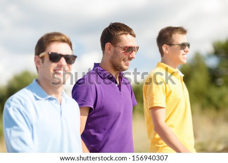 summer, holidays, vacation, happy people concept - group of friends walking on the beach