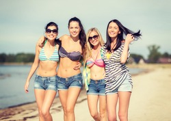 summer, holidays, vacation, happy people concept - group of girls in bikinis walking on the beach
