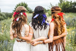 Summer holidays, vacation, travel and people concept - three beautiful hippie girl, photographed from behind, hairstyles, feathers, white dresses, flash tattoo, accessories, Bohemian Bo-ho Style indie