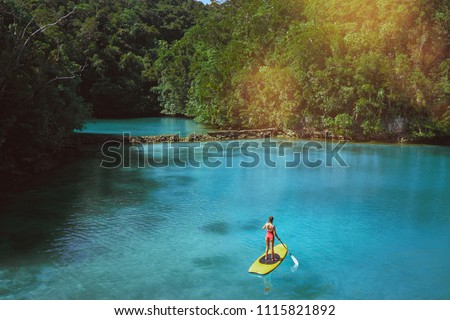 Summer holidays vacation travel. SUP Stand up paddle board. Young woman sailing on beautiful calm lagoon. - Shutterstock ID 1115821892