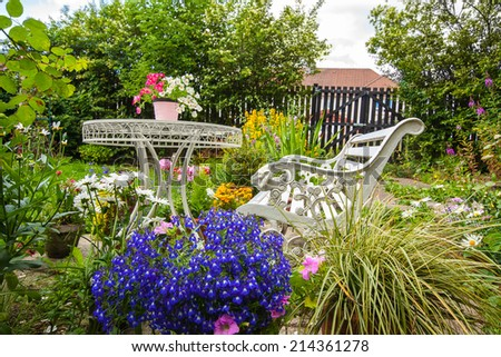 Summer home garden with white bench and a table