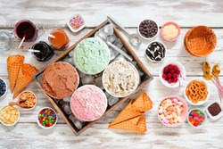 Summer ice cream bar with a selection of ice cream flavors and dessert toppings. Top view table scene on a rustic white wood background.