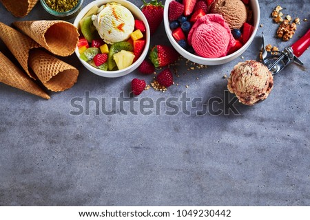 Summer ice cream flavors with fresh fruit salad, assorted berries, nuts, sugar cones and a scoop as a border on textured slate with copy space #1049230442
