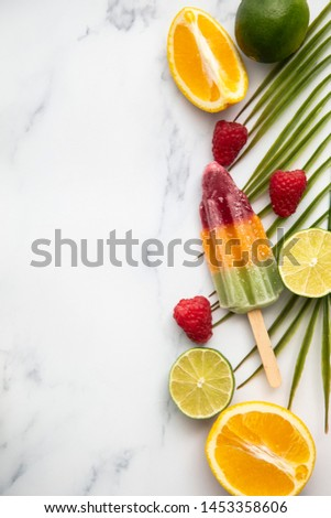 Summer ice lollies with fruit and a tropical palm leaf