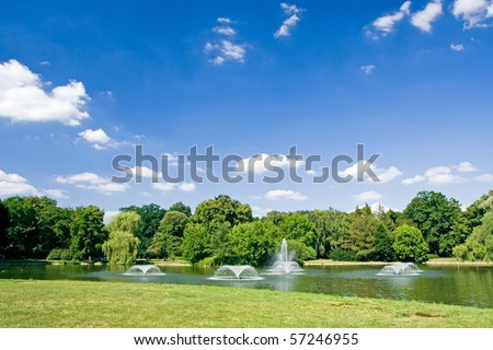 Summer in park with pond and fountains over blue sky