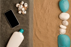 summer in the beach concept, cris towel on beach sand, black screen smartphone, bottle of cream and white shells. beach sand .top view. space for text
