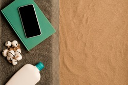 summer in the beach concept, cris towel on beach sand, on top of turquoise book with smartphone black screen, bottle of cream. beach sand .top view. space for text