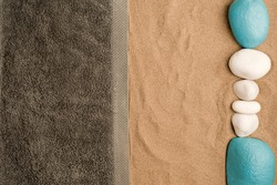 summer in the beach concept, cris towel on beach sand, on top of white and turquoise stones sand. beach sand .top view. space for text