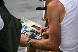Summer. Italy. Florence. The street artist paints a picture with oil paints and a thin brush.