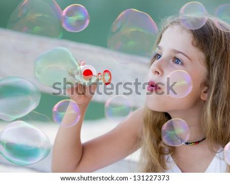 Summer joy, happy child - Soap bubbles - lovely girl blowing bubbles