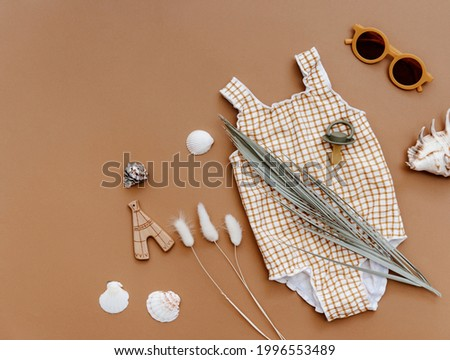Summer kids accessories on brown background. Cute retro swimsuit, straw hat, sunglasses and seashells, summer concept flat lay  Photo stock ©