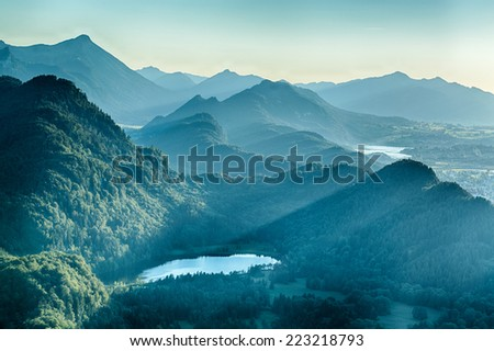 Summer landscape by dusk - the Schwansee surrounded by mountain hills and peaks. #223218793