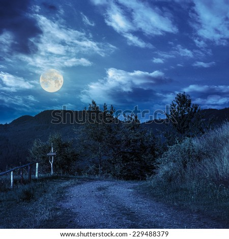 summer landscape. fence near the path on the hillside in high mountain at night in full moon light