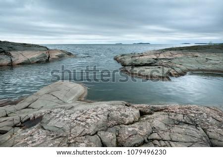 Summer landscape. Granite banks, stony stones, a small lagoon with dark water, a dark overcast sky and islands on the horizon. Russia, Finland, Karelia, Lake Ladoga