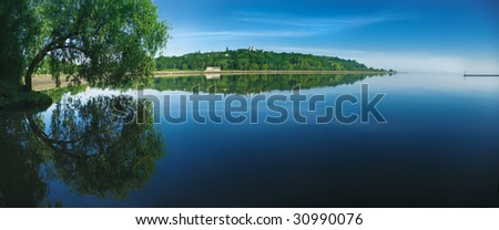 Summer landscape. Green trees reflected in the Dnieper river near the Kiev city.
