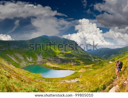 Summer landscape in the mountains near the lake with photographer