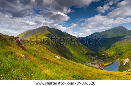 Summer landscape in the mountains. Young boy looking at the lake - stock photo