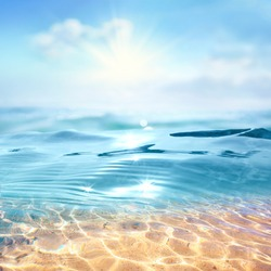 Summer landscape, nature of tropical with rays of sun light. Beautiful sun glare in wave of transparent blue water on beach against blue sky. Copy space, summer vacation concept.