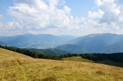 Summer landscape of a forested mountain range and grassy valleys under a cloudy sky. The village of Kolochava and Mount Strymba in the background. Carpathian mountains, Transcarpathia, Ukraine