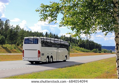 Summer landscape of a white bus traveling on motorway on a beautiful day with blue sky and clouds, and a defocused birch tree in the foreground.  #684054094