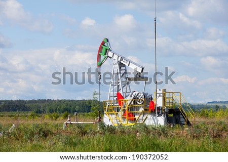 summer landscape oil pump in a green field, cloudy sky above him and the forest on the horizon