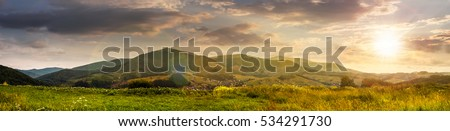 Summer landscape panoramic image of rural fields in mountains under cloudy sky in evening light #534291730