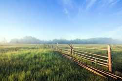 summer landscape thick fog in the field and an old wooden fence