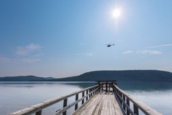 Summer landscape. View of the Angara River and mountains from a wooden boat pier on a sunny summer day. A small helicopter is flying in the sky. Taltsy village, Irkutsk region, Russia.